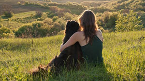 Women hugging dog on a hill